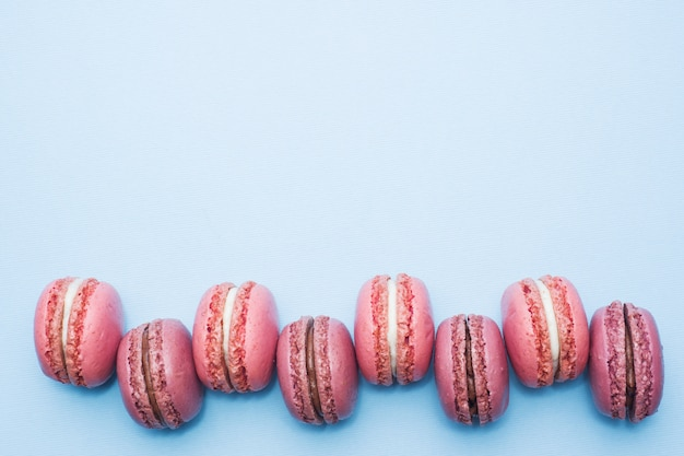 Pink dessert macaron or macaroon on blue background top view with flat lay