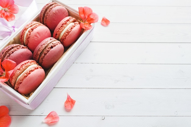 Pink dessert macaron or macaroons in a box on a white table. copy space.