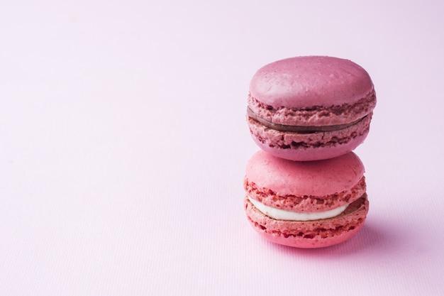 Pink dessert macaron or macaroons on pink background.