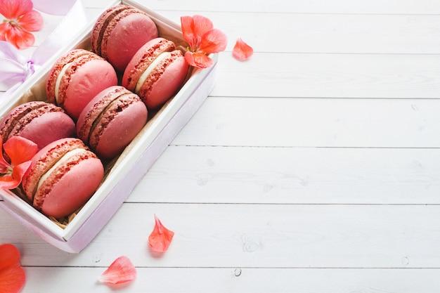 ピンクのデザートマカロンまたは白いテーブルの上のボックスにマカロン。コピースペース。