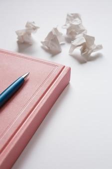 Розовый дневник и синяя металлическая ручка на белых мятых листах бумаги