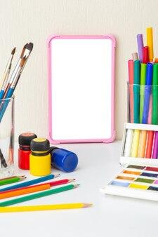 Розовый цифровой планшет с пустым экраном на белом столе с разноцветными принадлежностями для рисования.