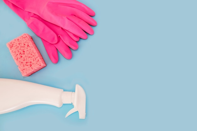 Pink dishwashing sponge, gloves and spray in a bottle on a blue surface