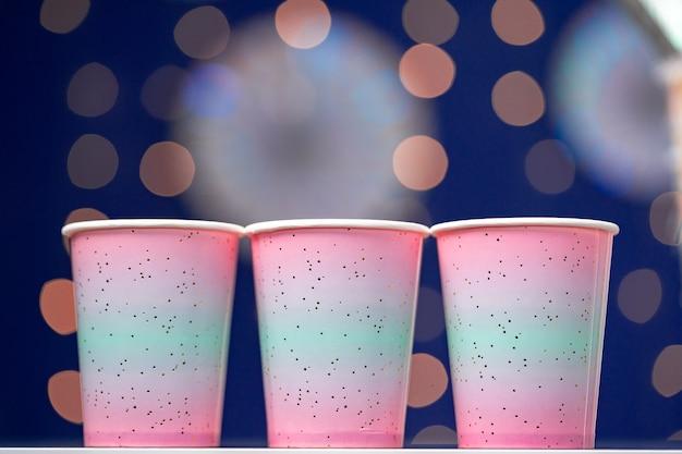青いボケ味の背景にピンクの使い捨てカップ、コピースペース