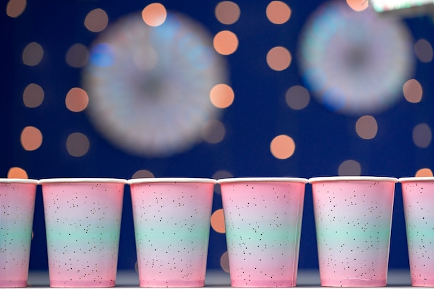 青いボケ味の背景にピンクの使い捨てカップ