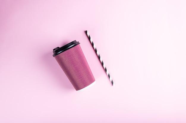 Розовый одноразовый бумажный стаканчик с полосатой бумажной соломкой