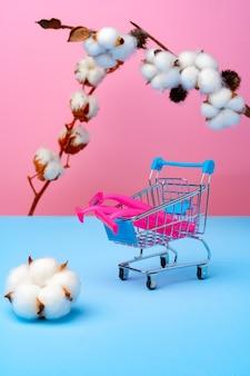 파란색 종이에 분홍색 일회용 면도기와 목화 꽃