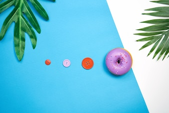 Pink donut and colorful on a blue background. creative food minimalism.