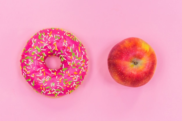Pink donut and apple, healthy eating
