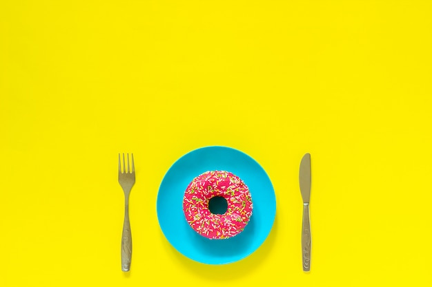 Pink donut on blue plate and cutlery knife fork on yellow background.
