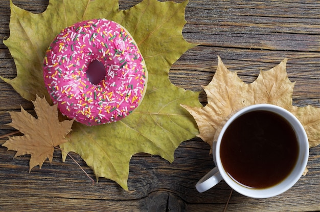 Pink donut, coffee cup and autumn leaves on old wooden background, top view