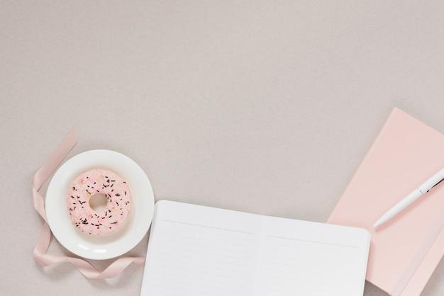 白い皿にピンクのドーナツとペンでピンクの日記、きれいなページのノート