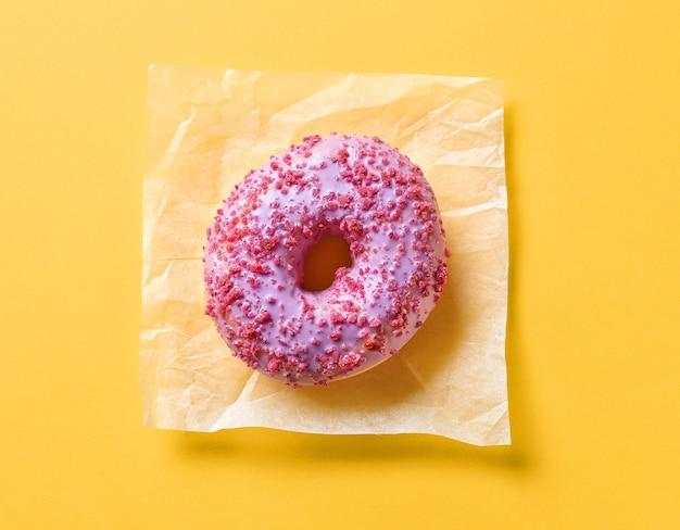 노란색 종이 배경에 핑크 도넛, 상위 뷰