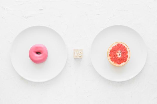 背景の上に白いプレート上のピンクのドーナツと半分のグレープフルーツ