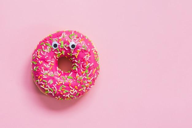 분홍색 배경에 눈을 가진 핑크 도넛