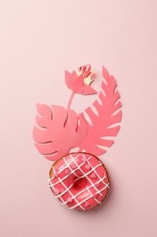 Pink donut with icing and origami paper craft modern flowers decor, on pink background, monochrome