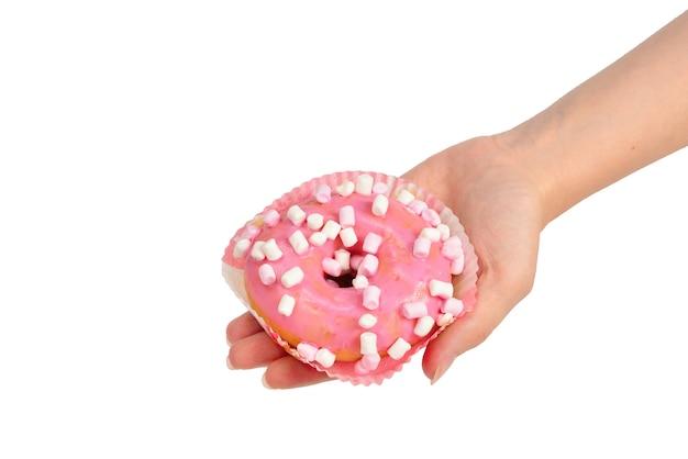 Розовый пончик с зефиром в женской руке, изолированной на белом
