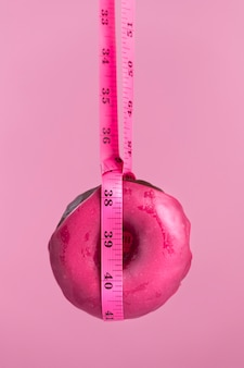 Pink donut with measuring tape