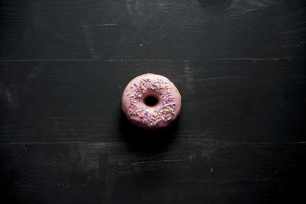 Ciambella rosa con scintillii su una superficie nera