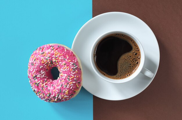 ツートンカラーの背景の上面図に振りかけるとコーヒーのカップとピンクのドーナツ