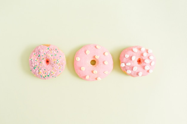 Pink donuts on green. flat lay, top view minimal pattern.