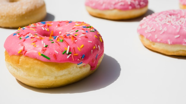 Pink donuts with colorful sprinkles on white background