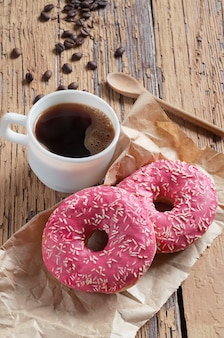 振りかけるピンクのドーナツと一杯のコーヒー