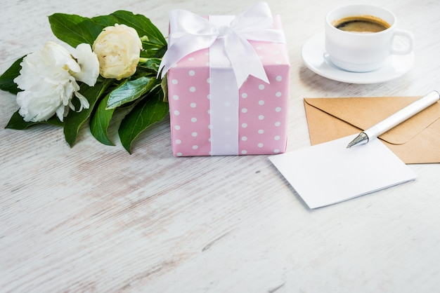 Pink dotted gift box, empty greeting card, kraft envelope, peonies bouquet and coffee cup over white wooden rustic table.