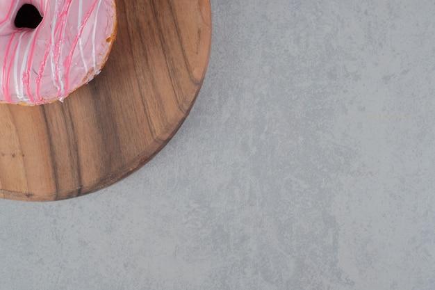 Ciambella rosa su una superficie di cemento
