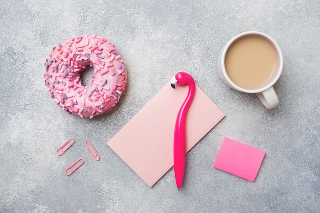 Pink doughnut and cup of coffee flamingo pen. top view flat lay.