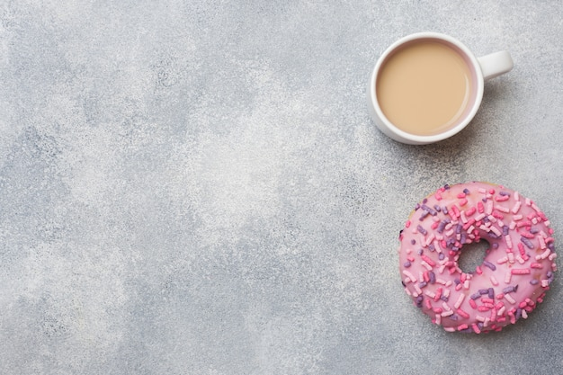 Pink doughnut and cup of coffee. top view flat lay. background with copyspace