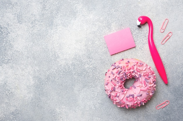 Pink doughnut and flamingo pen. top view flat lay.