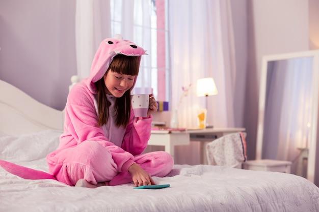 Розовый дракон. веселая маленькая самка сидит на кровати и наслаждается горячим какао