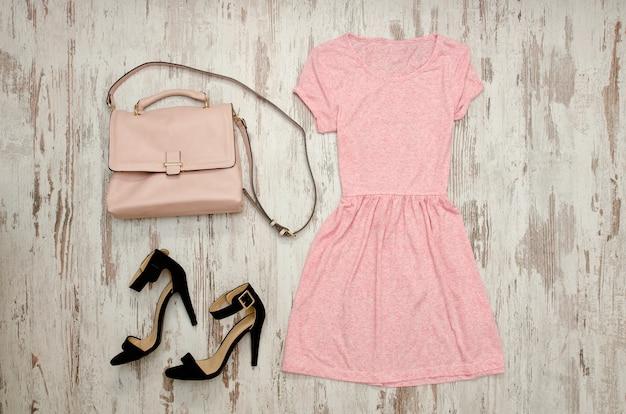 Розовое платье с черными туфлями и бежевой сумкой