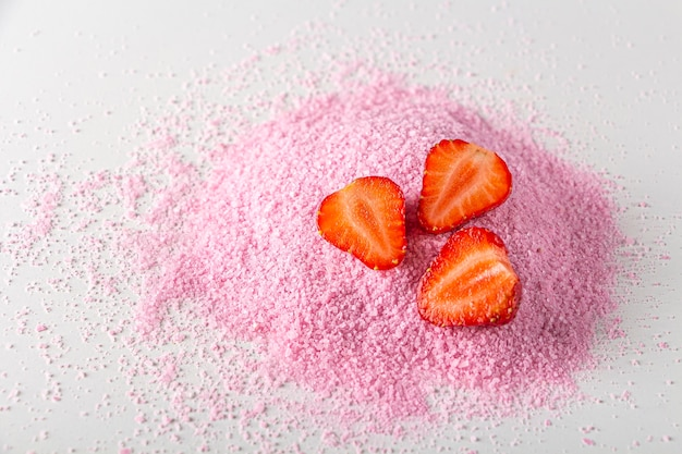 Pink dried strawberries powder with fresh raw berries on white background