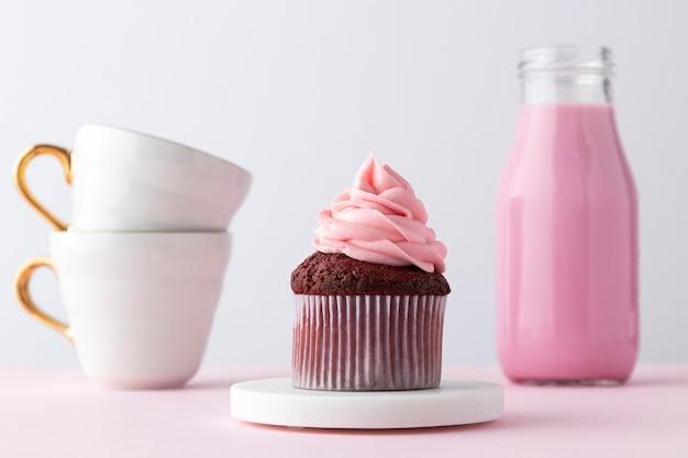 Розовый напиток, кекс и чашки