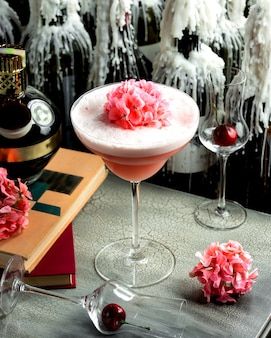 Pink drink with foam in a glass and pink flowers on it