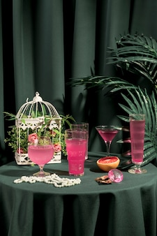Pink drinks next to fashion ornaments on table