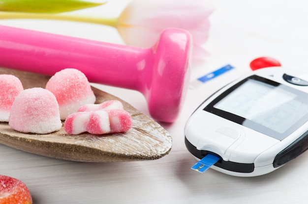 Pink dumbbell, sweets and glucose meter
