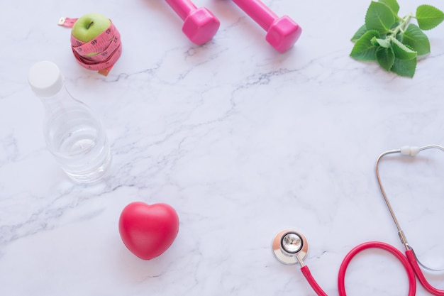 Pink dumbbell with red heart and stethoscope and green apple on white marble background