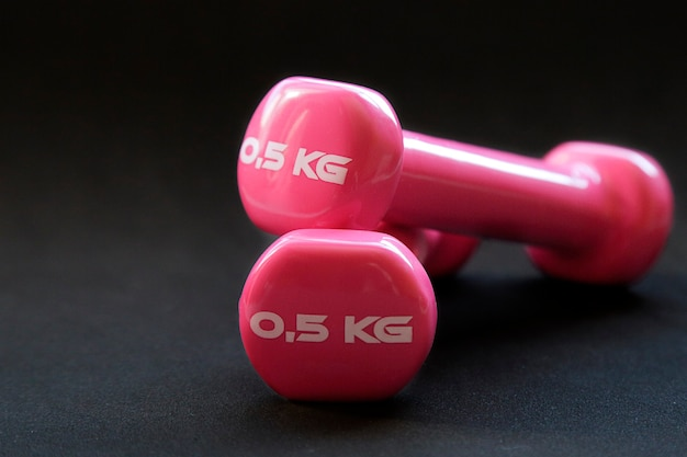 Pink dumbbells for fitness weighing 0.5 kg over a black background
