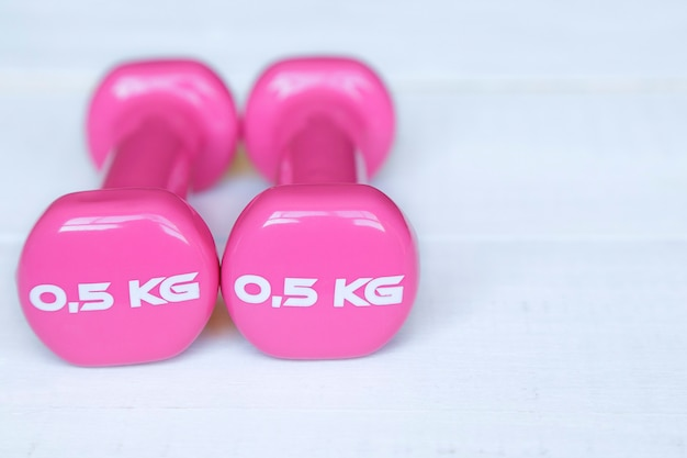 Pink dumbbells for fitness weighing 0.5 kg over a white wooden table