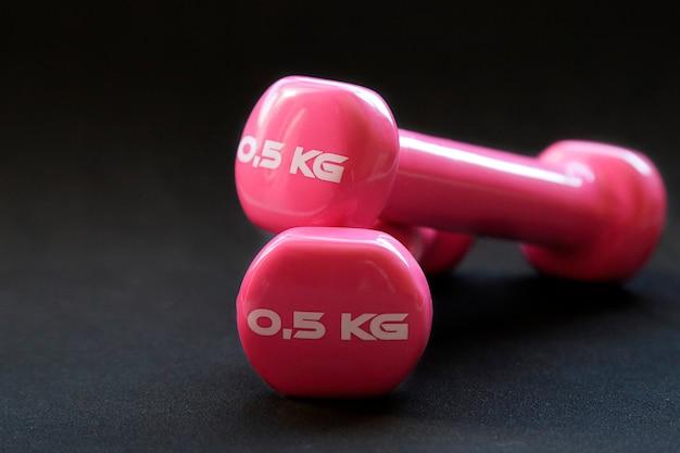 黒の背景の上に0.5kgの重さのフィットネス用のピンクのダンベル
