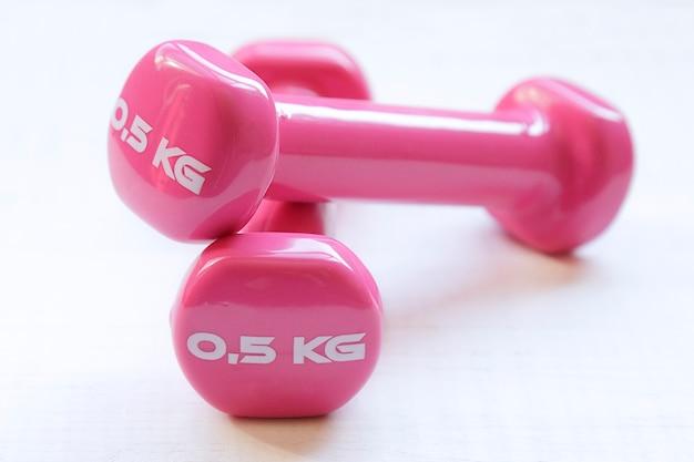 白い木製のテーブルの上に体重0.5kgのフィットネス用のピンクのダンベル