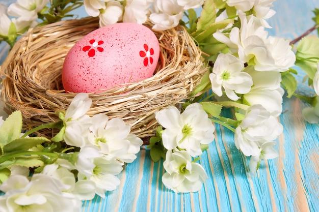 짚 둥지와 푸른 나무 배경에 꽃 지점에 분홍색 부활절 달걀