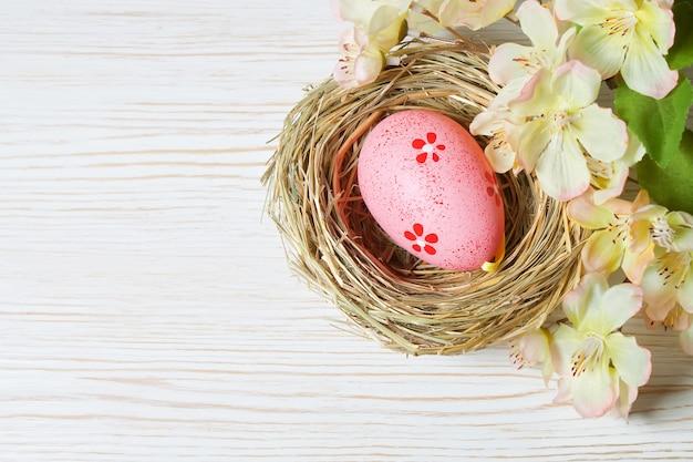 짚 둥지와 흰색 나무 바탕에 꽃 지점에 분홍색 부활절 달걀. 상위 뷰, 텍스트를위한 공간이있는 평면 배치.