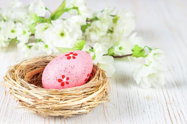짚 둥지와 흰색 나무 테이블에 꽃 지점에 분홍색 부활절 달걀.