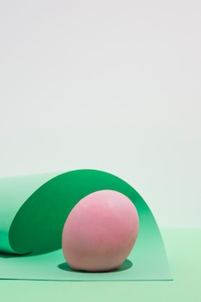 Pink easter egg with paper sheet on light table