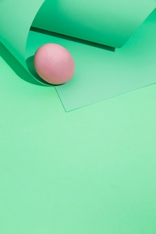 Pink easter egg with rolled paper on table