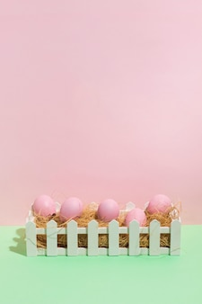 Pink easter eggs on hay in box on table